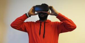 man in a red sweater looking into an oculus device